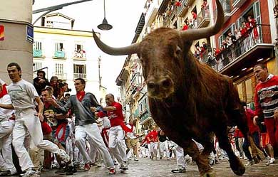 RUNNERS LEAD FIGHTING BULLS AROUND ESTAFETAS BEND DURING RUNNING OF THE BULLS IN PAMPLONA